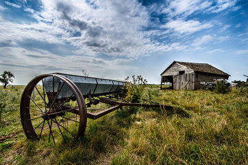 OLD BROKEN DOWN SHACK AND ANCIENT STEEL WHEELED FARM TOOL