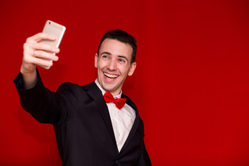 Stylish man in suit taking selfie on smartphone. Young man with funny facial expressions isolated on red background