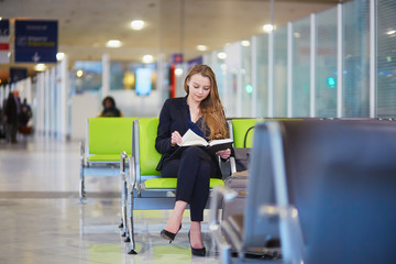 Woman in international airport reading a book
