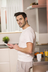 young man in home kitchen with tablet