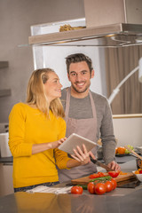 Attractive couple in home kitchen with digital tablet