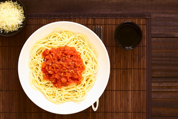 Traditional Italian Spaghetti alla Marinara (spaghetti with tomato sauce) in bowl with red wine and grated cheese on the side, photographed overhead on dark wood with natural light