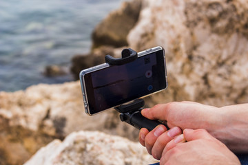 Man holding a smart phone filming the beach in Villefranche-sur-mer, France