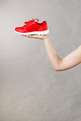 Woman presenting sportswear trainers shoes