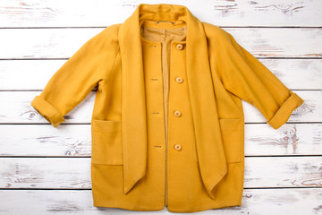 Female elegant yellow cashmere topcoat. Women fashion autumn apparel on white wooden background. Feminine fashion and style.