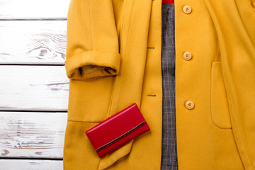 Female cashmere overcoat of yellow color. Women classy topcoat and red purse on wooden background close up.