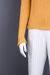 Yellow sweater and white trousers for women. Mannequin in casual female clothes, cropped image.