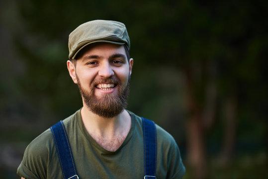 Handsome smiling bearded man in green hat in garden