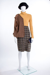 Female mannequin in casual outfit. Women black hat, sweater, skirt and brown waistcoat on shoulder. Boutique of feminine garment.