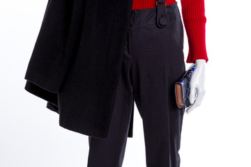 Close up female coat, trousers, wallet. Red sweater and black trousers, cropped image.