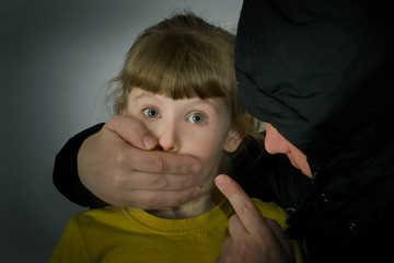 Man closed his mouth on the child's hand.Kidnapping conceptual photography.