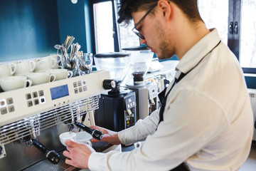 Barista making coffee using a modern coffee maker. High key image