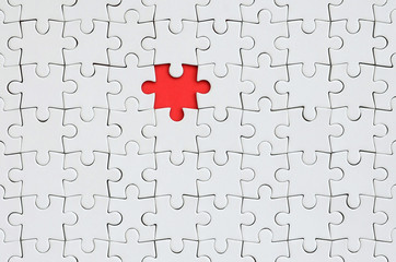 The texture of a white jigsaw puzzle in an assembled state with one missing element forming a red space