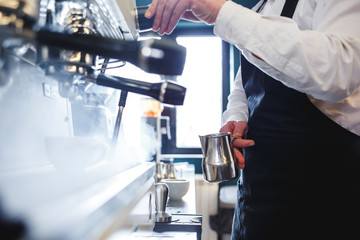 Barista holding a silver pot and preparing milk for a cappuccino. High key image.