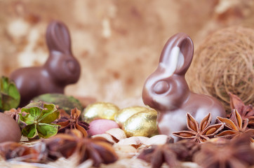 Easter bunnies, made of white and milk chocolate against a brown background.