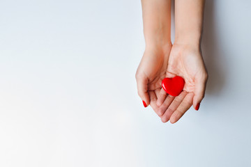 Red heart holding in female hands