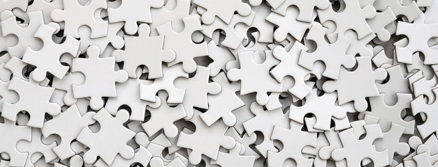 Close-up of a pile of uncompleted elements of a white puzzle. A huge number of rectangular pieces from one large white mosaic