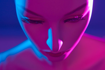 The head of a woman's dummy. Artificial Intelligence. A woman is a robot. Mannequin in neon light. Female mannequin. The head of a woman is made of plastic.