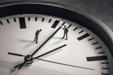 Two businessman standing in the middle of clock face. Business concept