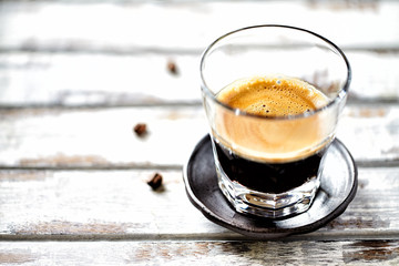 Glass of espresso on white wooden background