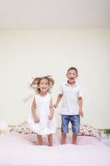 Family Values and Relationships. Happy Kids Playing Indoors. Jumping On The bed Together.Vertical Image Composition