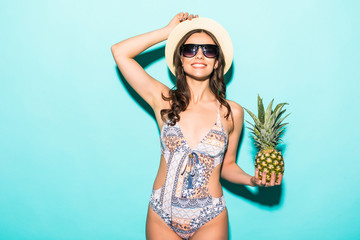 Portrait of young woman in swimsuit and sunglasses and hat with pineapple on green background. Summer season image concept