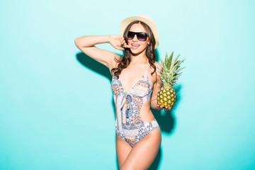 Portrait of young woman in swimsuit with pineapple on blue background. Summer season image concept