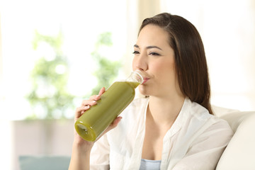Woman drinking a vegetable juice from a bottle