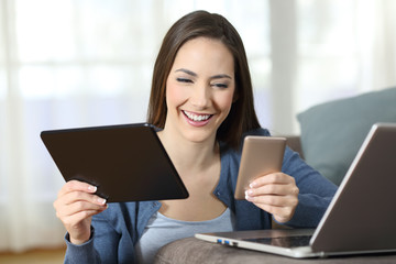 Woman using multiple devices on a couch at home