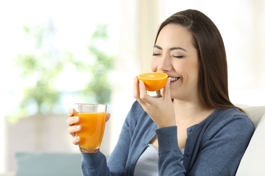 Woman smelling an orange and holding a juice
