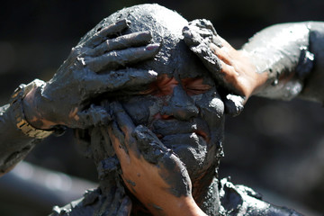 """A member of the """"Bloco Pretinhos do Mangue"""" (Block of Blackheads from Mud) group performs during carnival festivities in Curuca"""