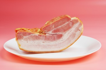 a large fatty piece of smoked bacon lies on plates on a pink background