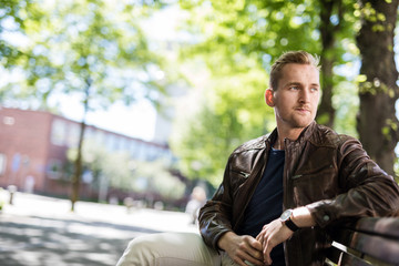Lonely man sitting down on a bench outdoors on a sunny day, wearing a blue shirt and brown leather jacket. Looking away from camera.