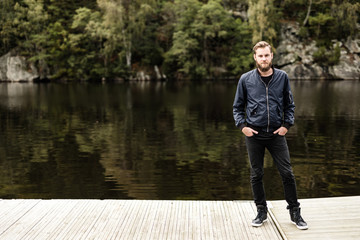 One bearded man wearing a blue jacket, standing in front of a lake and trees on a moody day.