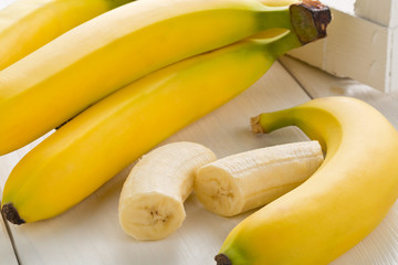 Bundle of fresh, ripe, yellow bananas with sliced banana pieces on table