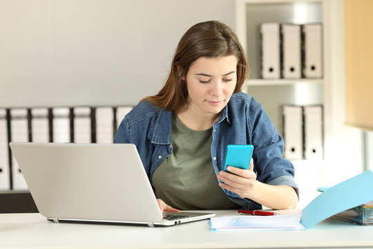 Intern checking phone message at office