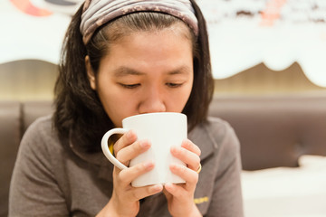 Young woman drink coffee in cafe with vintage tone.