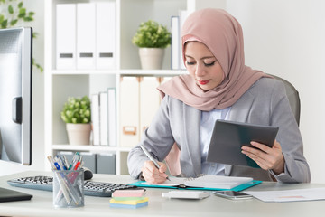 muslim business woman using mobile computer work
