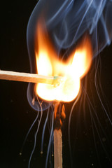 Two igniting matches against black background