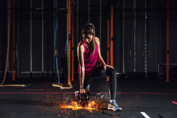 Athletic girl works out at the gym with a fiery kettlebell