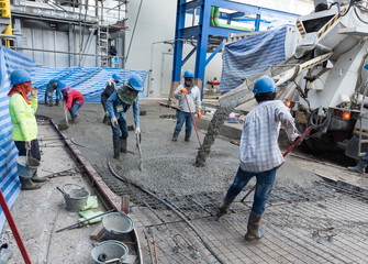 Workers at the construction site placing concrete slab