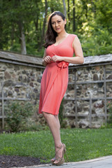 Stunning biracial (Asian and Caucasian) woman poses in garden in pink sun dress