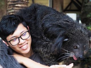 Asian man and binturong on his shoulder.