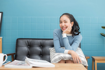 Beautiful Asian young woman sitting on sofa and smiling with copy space