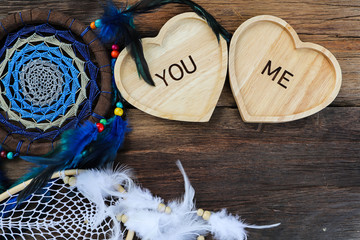 Wooden heart shape with the words YOU and ME on a tray on a wooden floor and a spacious feathers with copy space lovers concept.