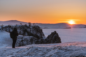 Travelling in winter at lake Baikal in Irkutsk, Russia. Winter landscape in sunset with young photographer enjoying beautiful sunset view in dusk