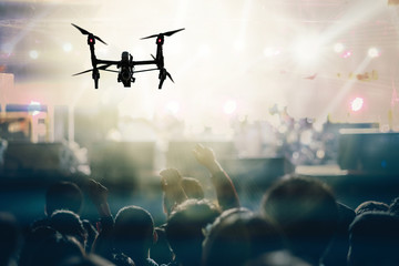 Closeup silhouette of Drone flying for taking video of Concert crowd and Music fanclub with show hand action which follow up the songer at the front of stage, musical and concert concept Wall mural