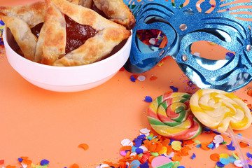 Purim background with carnival mask, party costume and hamantaschen cookies.