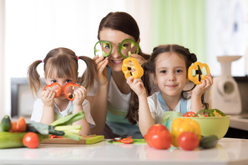 mother and kids daughters having fun in the kitchen