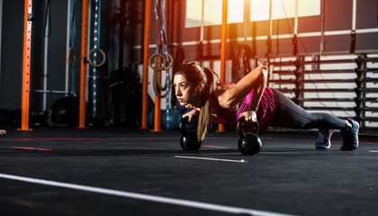Athletic girl works out at the gym with a kettlebell